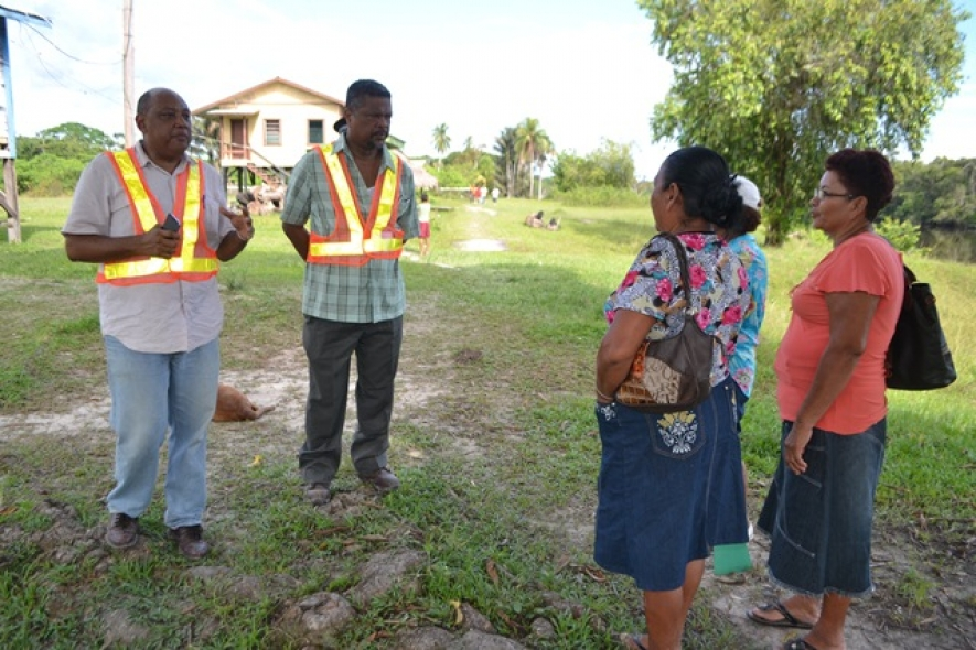 Minister of Governance, Raphael Trotman and Chief Labour Officer Charles Ogle speaking with a few residents of Wiruni. (June 29, 2015)