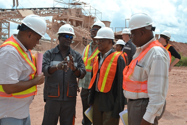 Minister of Governance, Raphael Trotman( at left) Member of Parliament for Region Ten, Audwin Rutherford (at right), Chief Labour Officer Charles Ogle (in plaid shirt), and Clayton Hall, Advisor to the Minister (second from right) being briefed by a RUSAL official at the Kurubuka 22 mine site. (June 29, 2015)